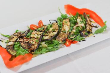 Melanzane - Thin Grilled eggplant marinated in oil, vinegar spices over arugula salad